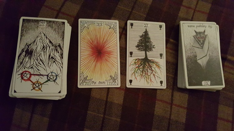 Four tarot cards laid out. The 3 of Pentacles, the Sun, The 6 of cups and the Hanged Man (Reversed)